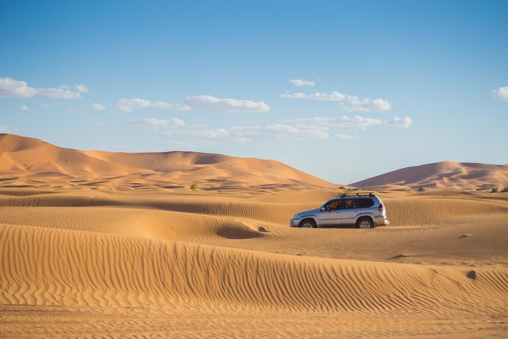 silver SUV on desert during daytime