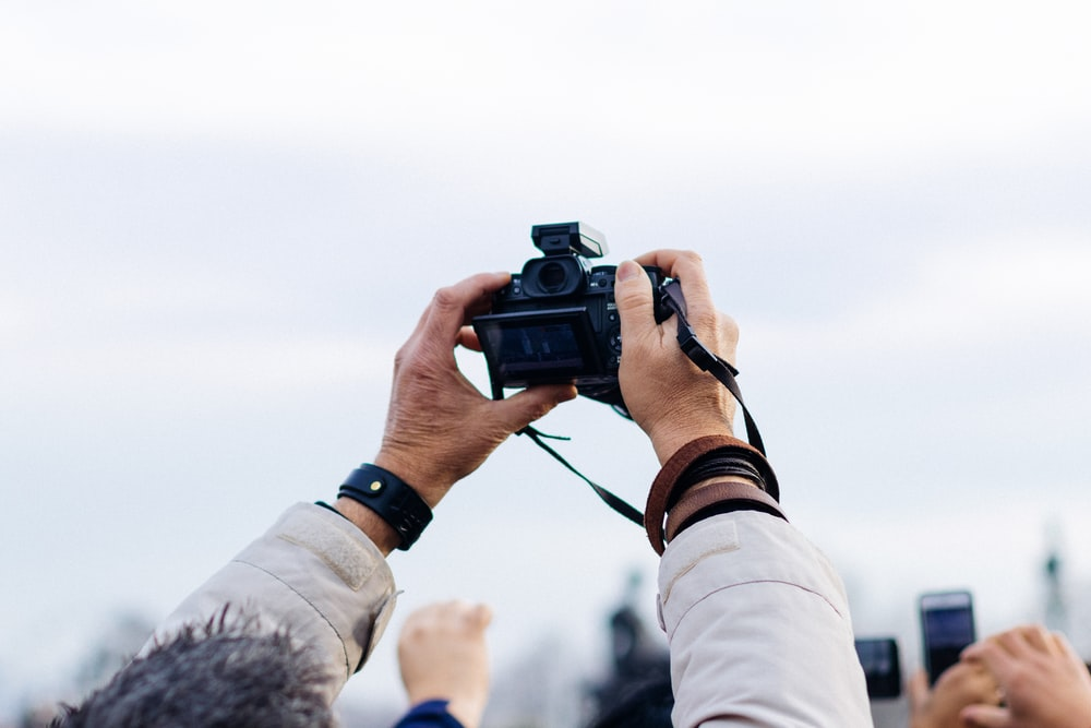 person holding black DSLR camera taking picture during daytime