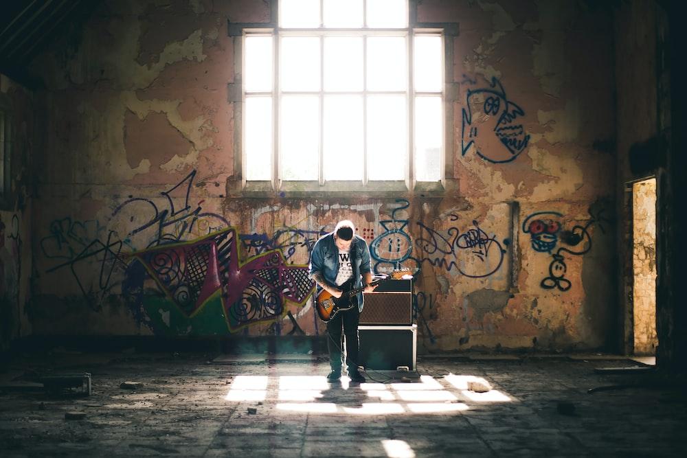 man playing guitar inside building