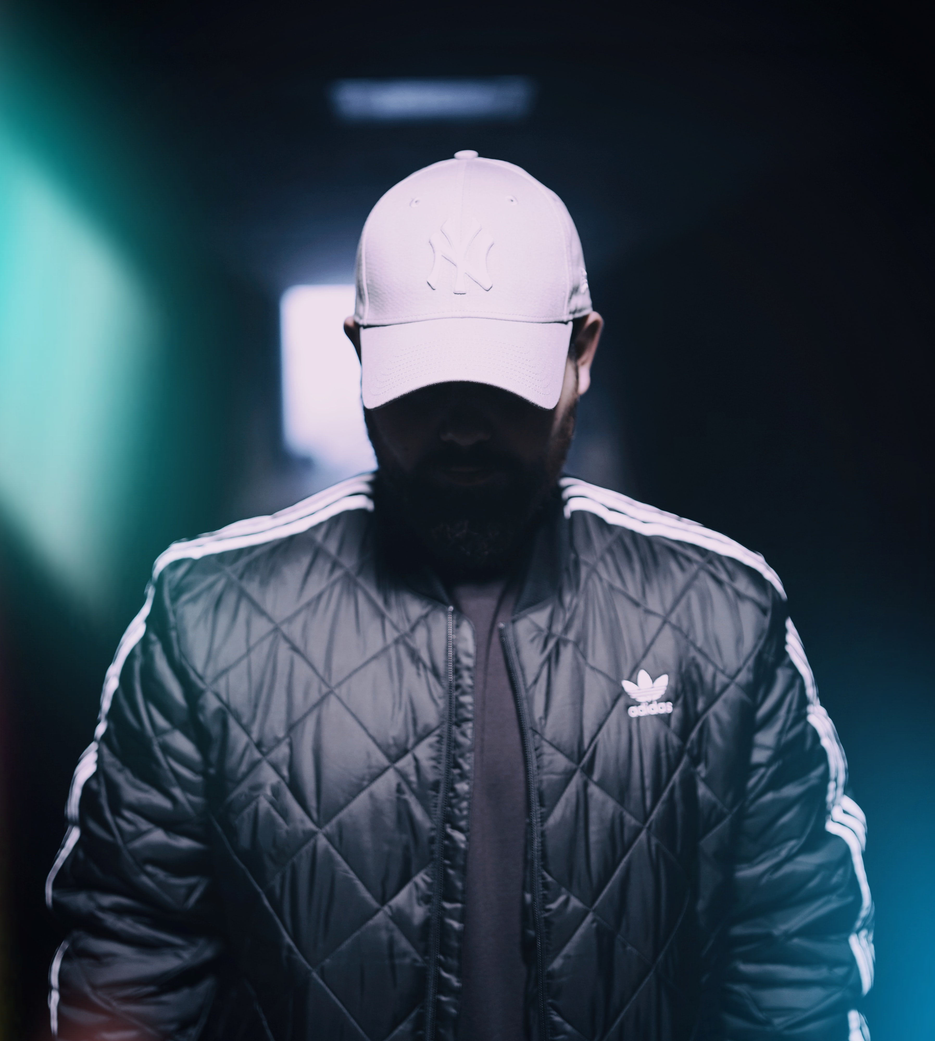 selective focus photograph of man in black adidas zip-up jacket and white New York Yankees curve-brimmed cap