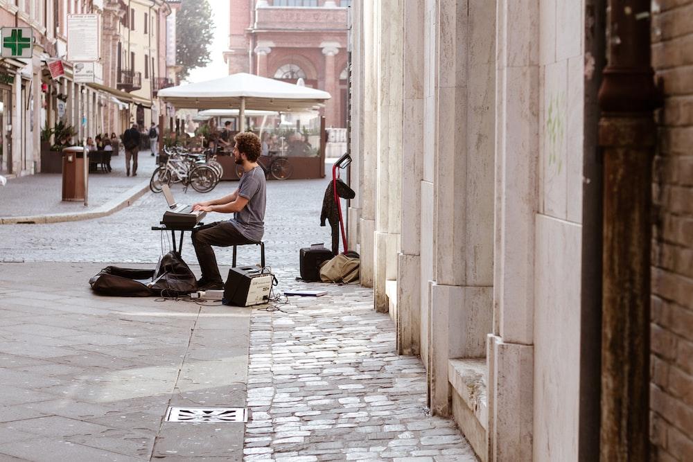 man playing keyboard on sidewalk