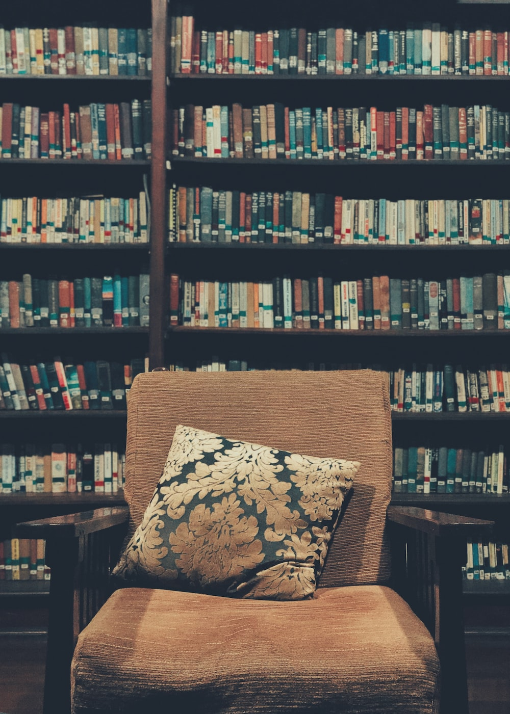 brown wooden armchair with books behind