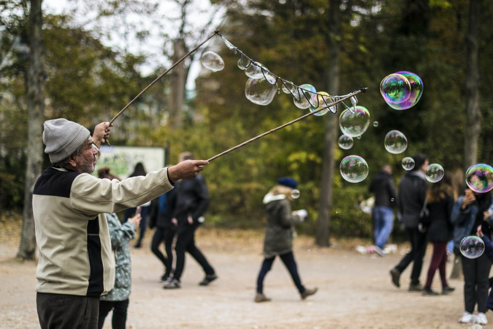 man holding stick while making bubbles