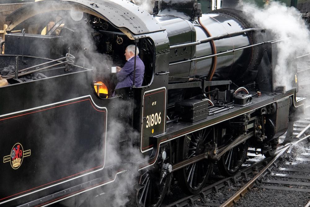 man standing inside steam train