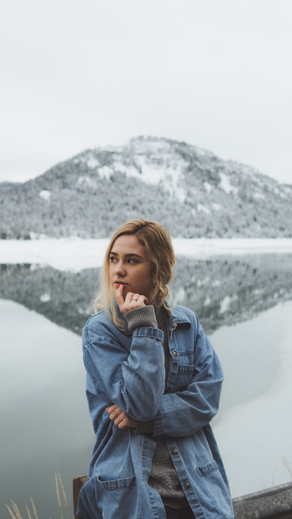 shallow focus photo of woman in blue denim jacket standing near mountain