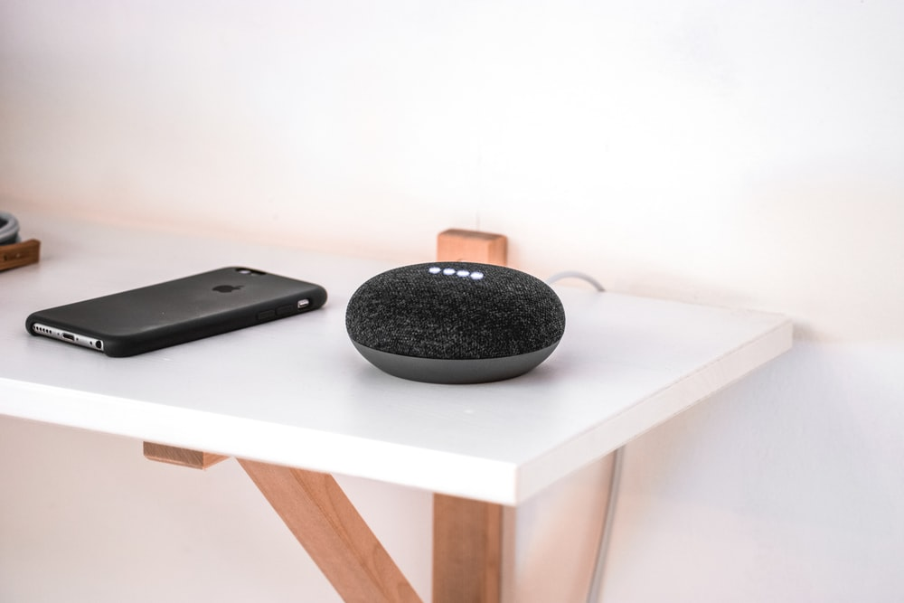 black iPhone on wooden table beside round portable speaker