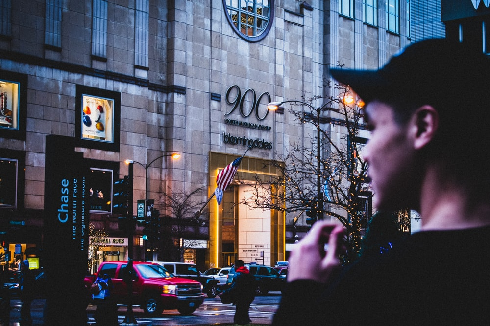 shallow focus photo of man standing in front of building
