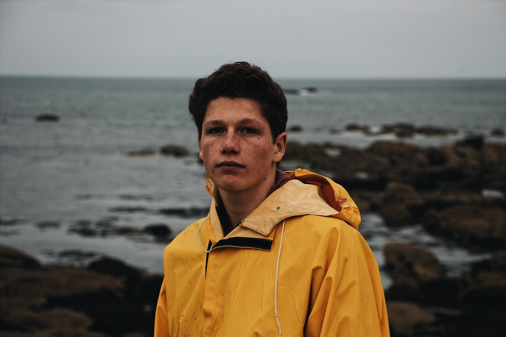 man in yellow jacket standing near sea during daytime