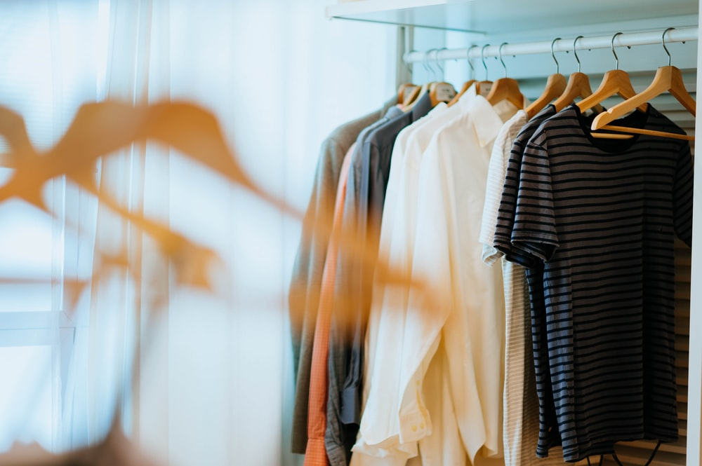 selective focus photography of shirts hanging on rack