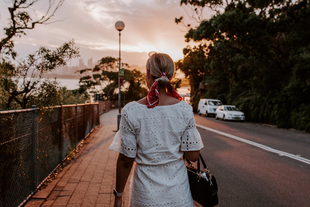 woman holding bag standing beside road