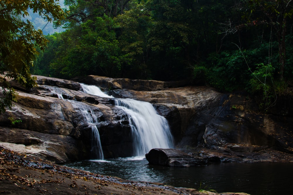 waterfalls in between trees during daytime