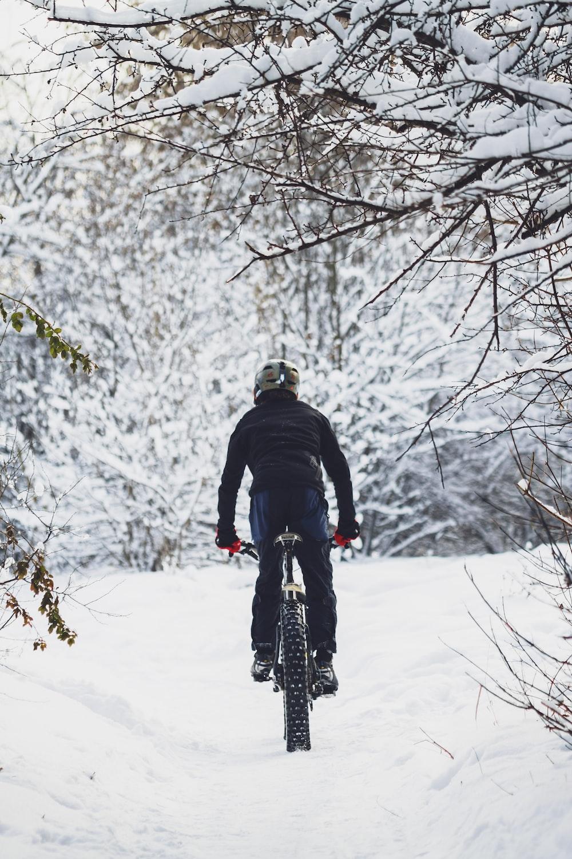 man riding bicycle on snow