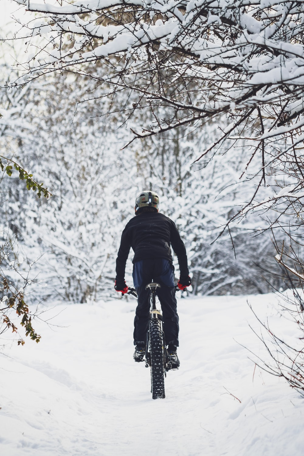 man riding bicycle on snow