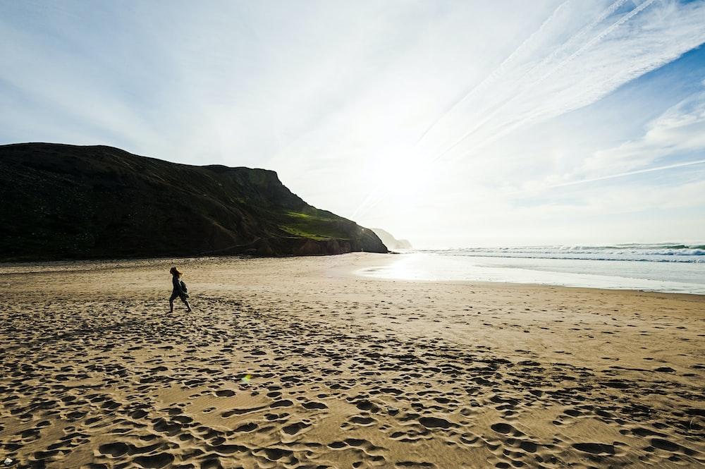 woman walking on brown beach sand