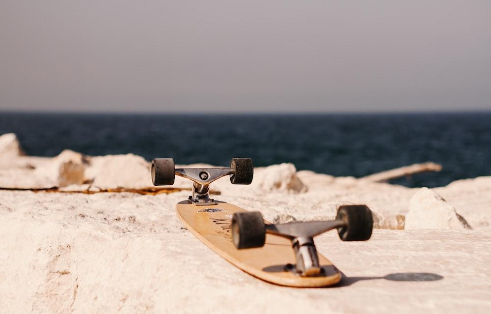 brown skateboard on concrete pavement