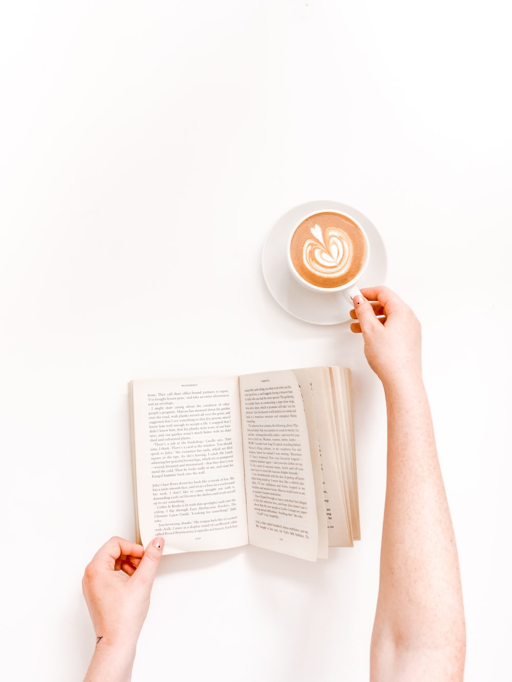 flat lay photography person holding mug with latte and book