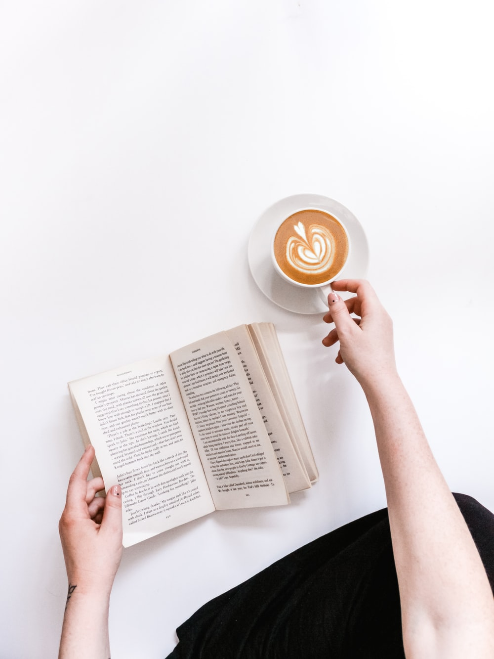 opened book and coffee on white surface