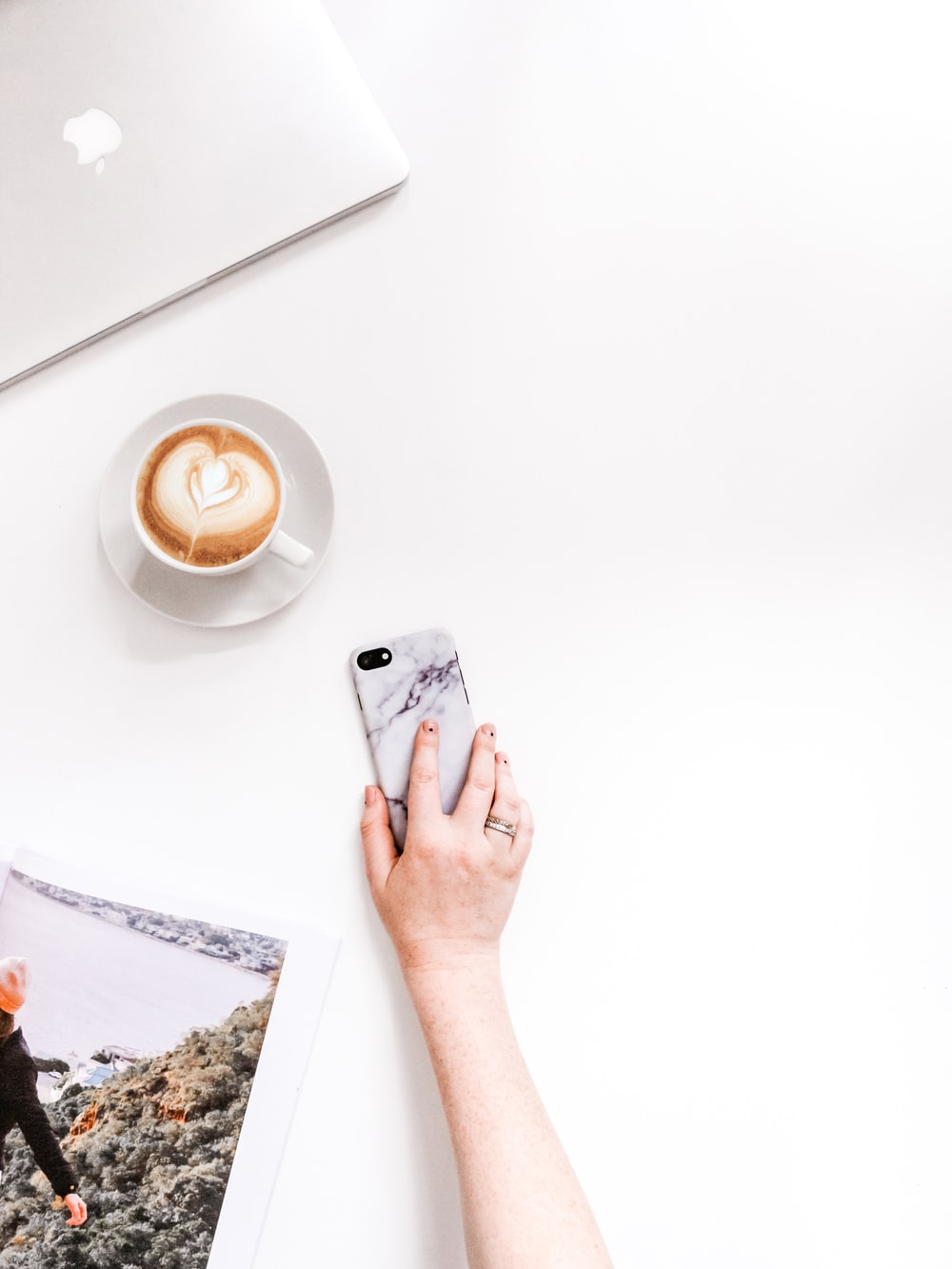 person holding smartphone near cup of coffee