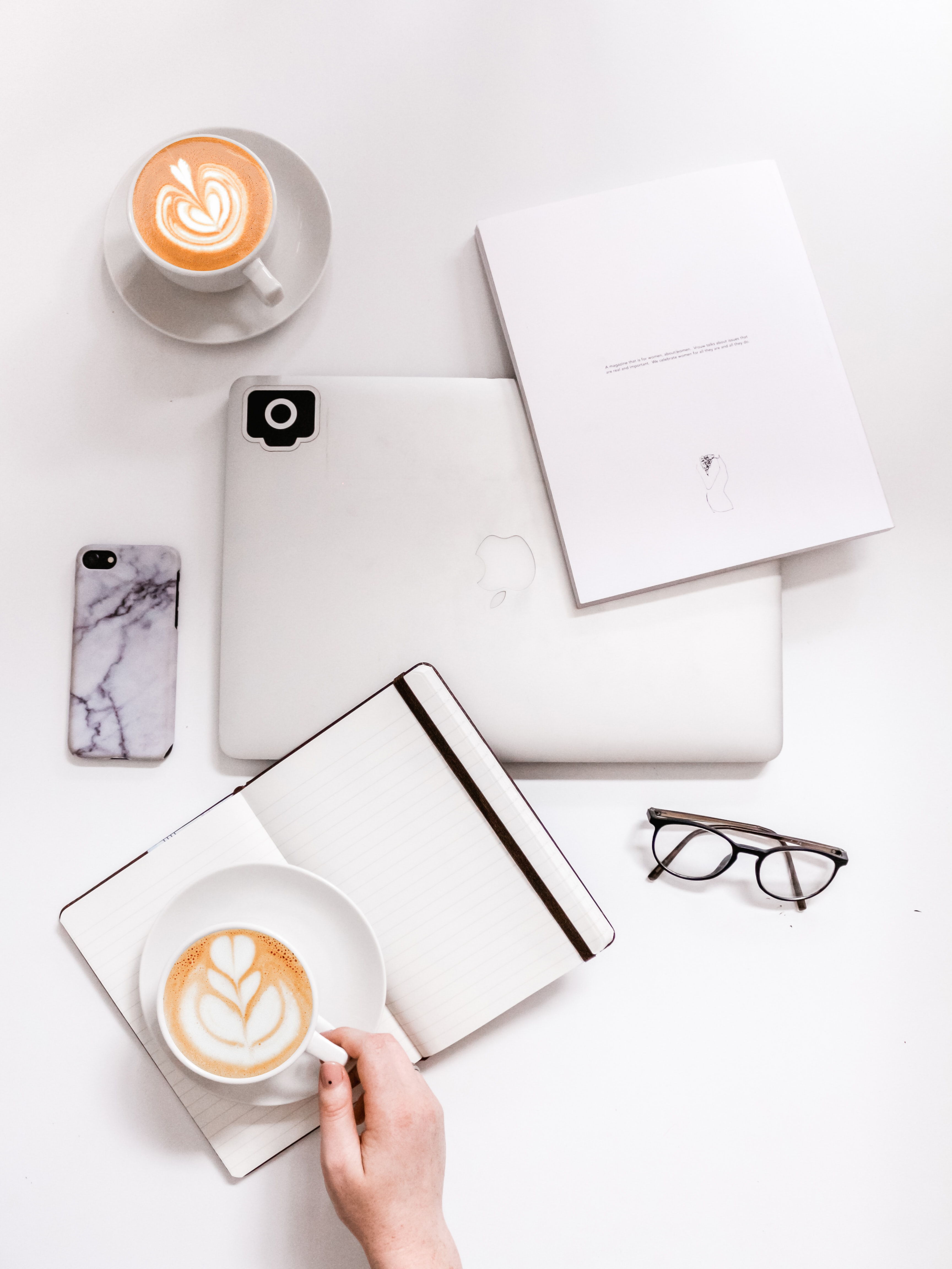 flat lay photography of coffee latte on top of open planner and MacBook