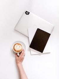 cappuccino beside closed MacBook