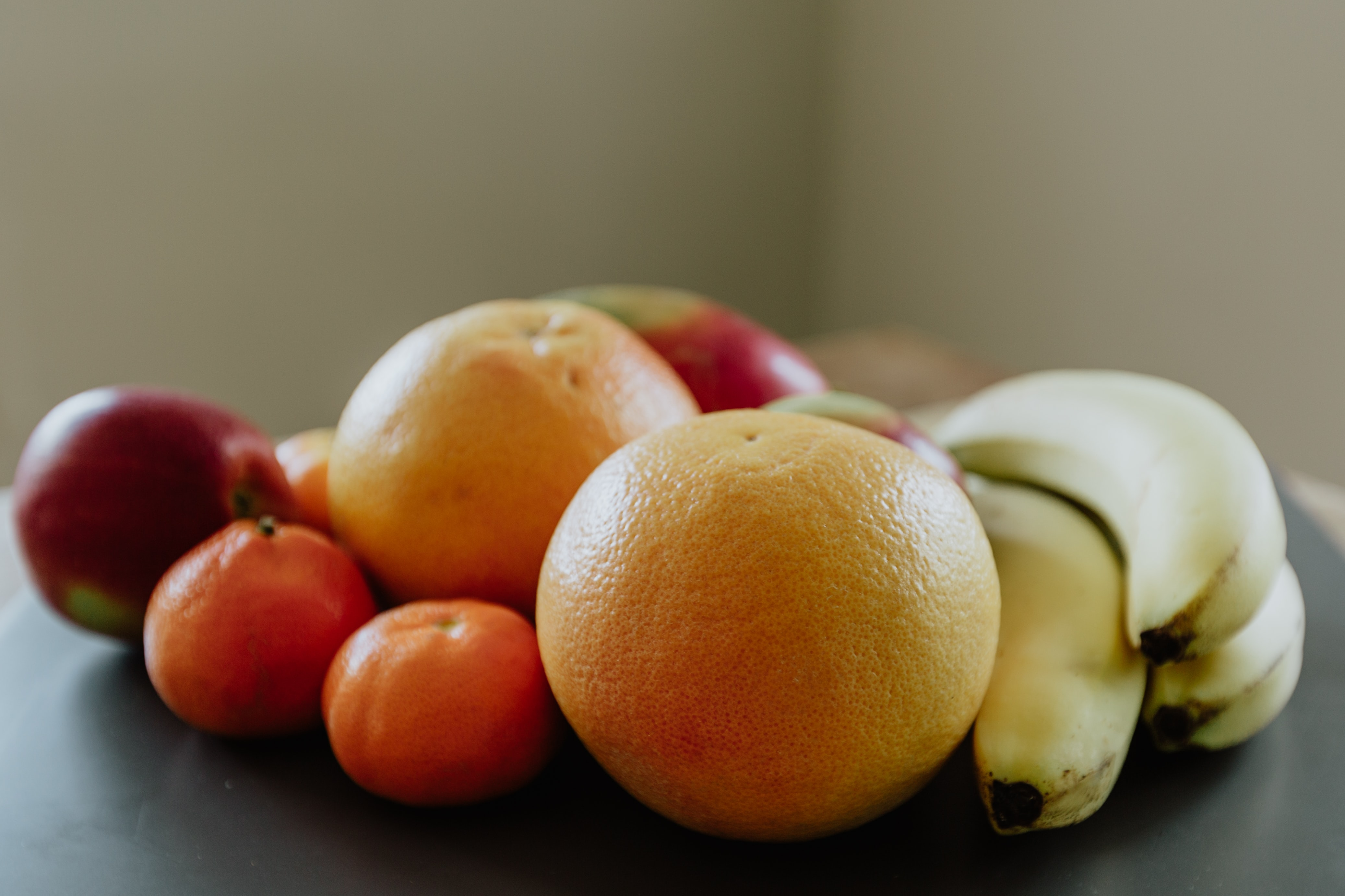 selective focus photography of banana, orange, and apple fruits