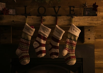 four assorted-color christmas socks stocking teams background