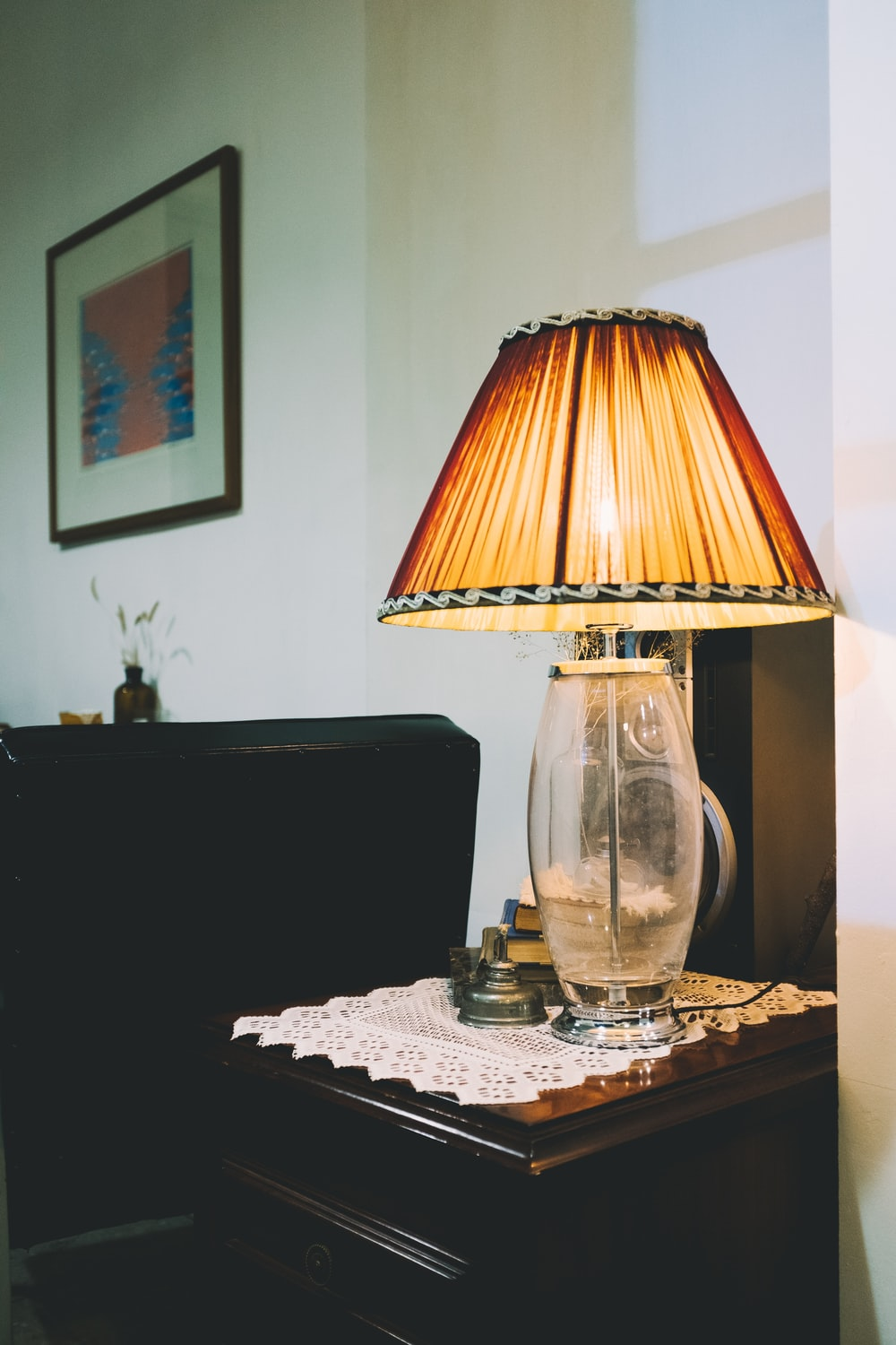 turned on clear glass table lamp on brown wooden end table