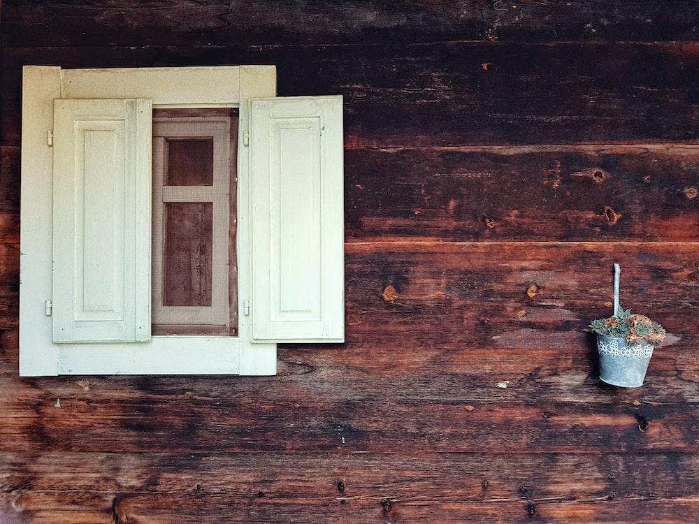 white wooden window beside bucket of flowers on wall