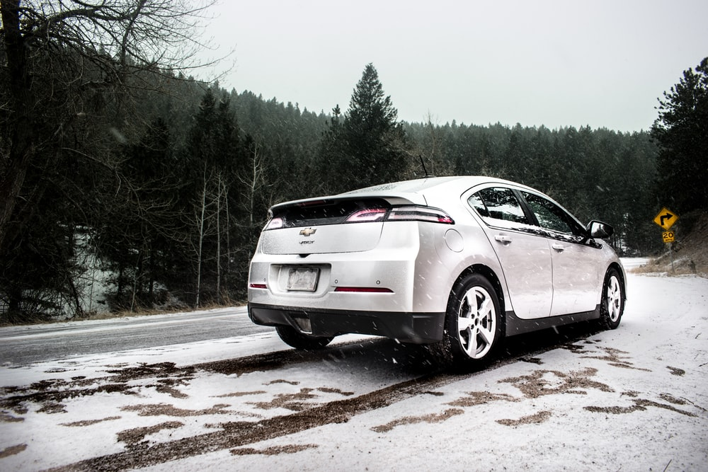 silver Chevrolet sedan on roadway near green leaf trees