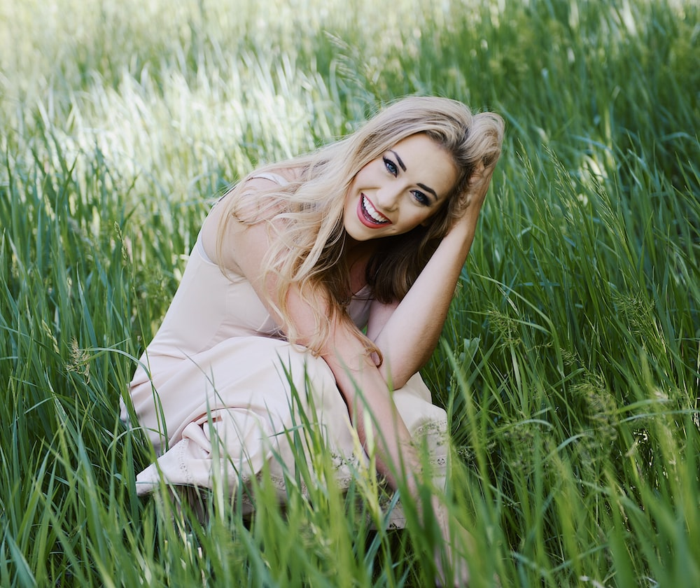 woman touching her hair and surrounded by grass