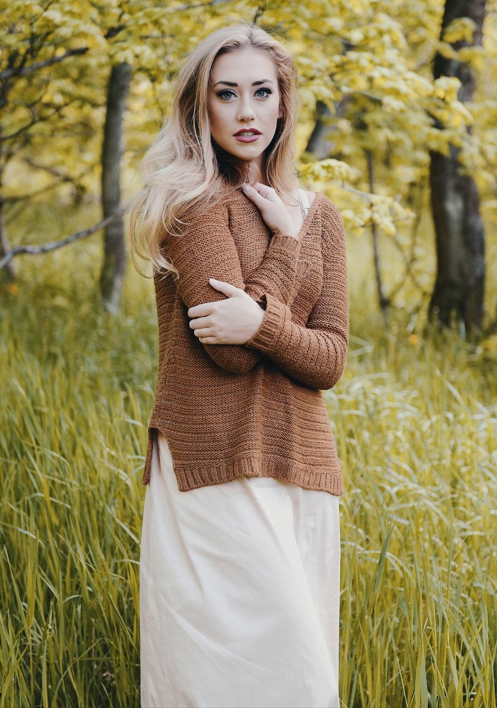 woman wearing brown sweater standing on green grass field
