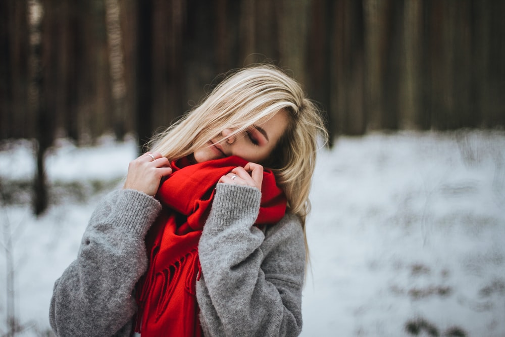 selective focus photography of woman touching red scarf
