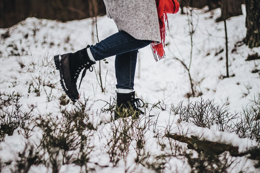 person walking on snow wearing black boots
