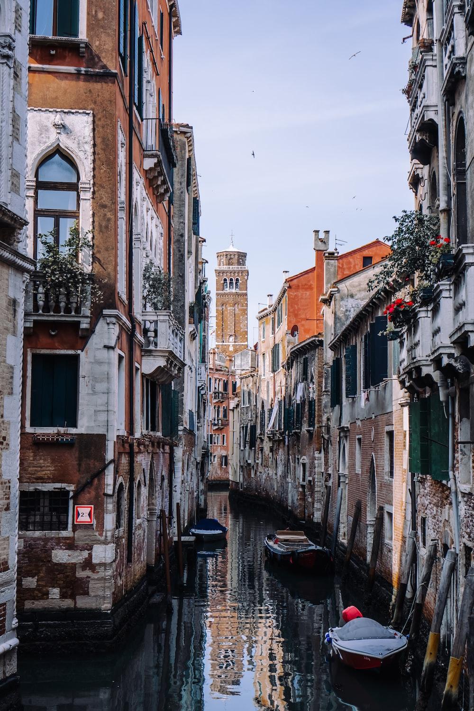 boat in between buildings during daytime