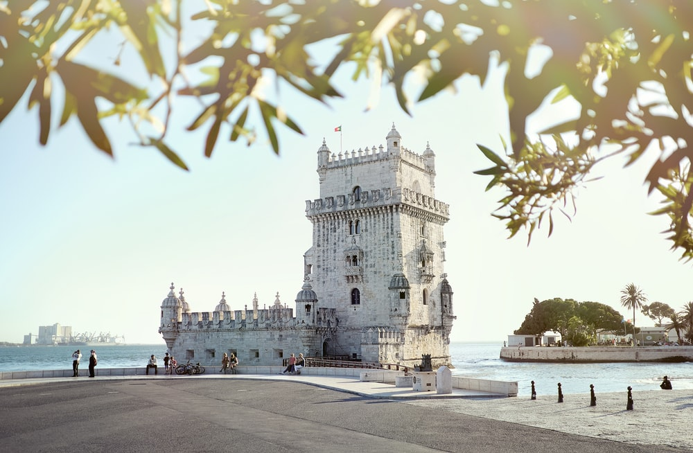 white concrete castle surround with body of water