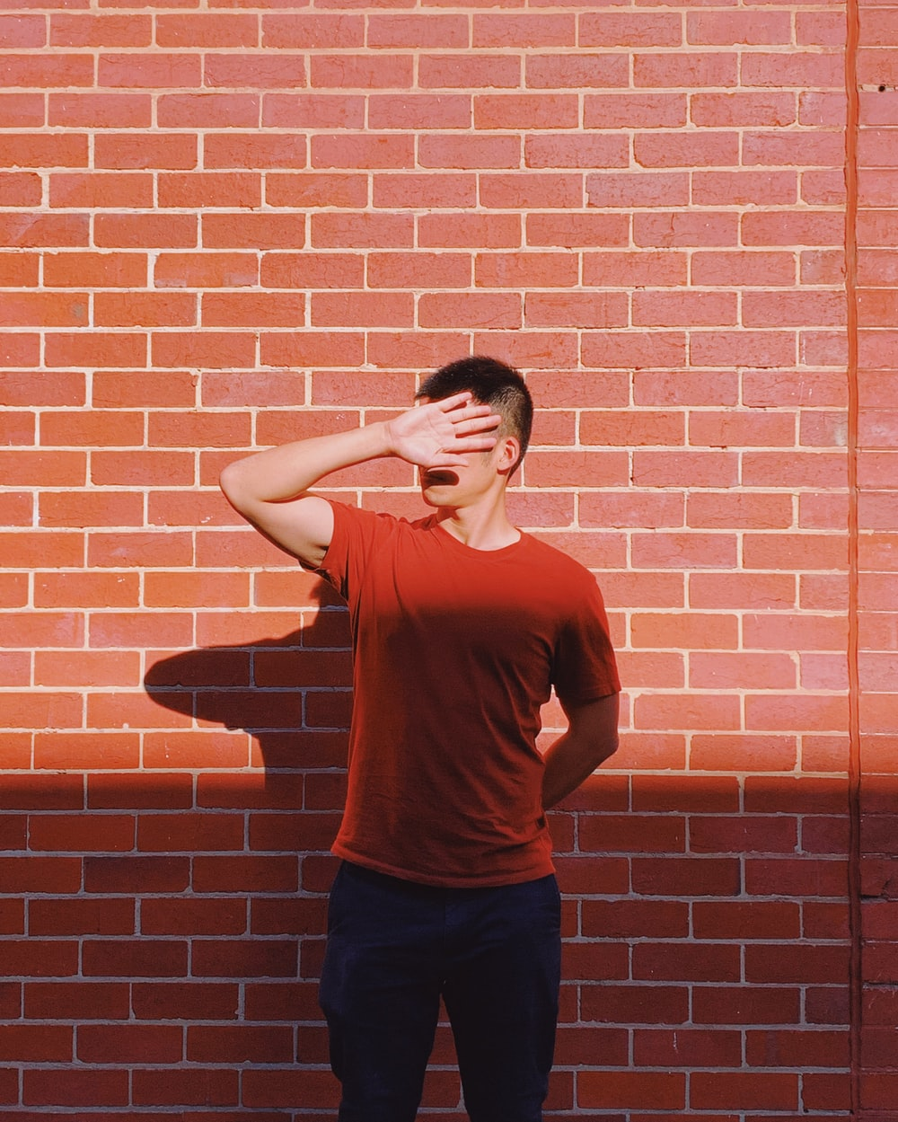 man standing in front of brick wall