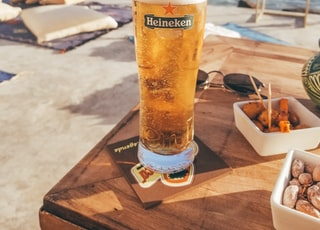 clear Heineken glass filled with yellow liquid on wooden table