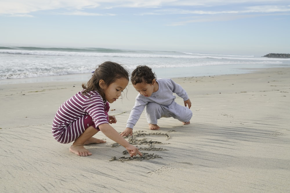 two kids playing and writing on sand near shore