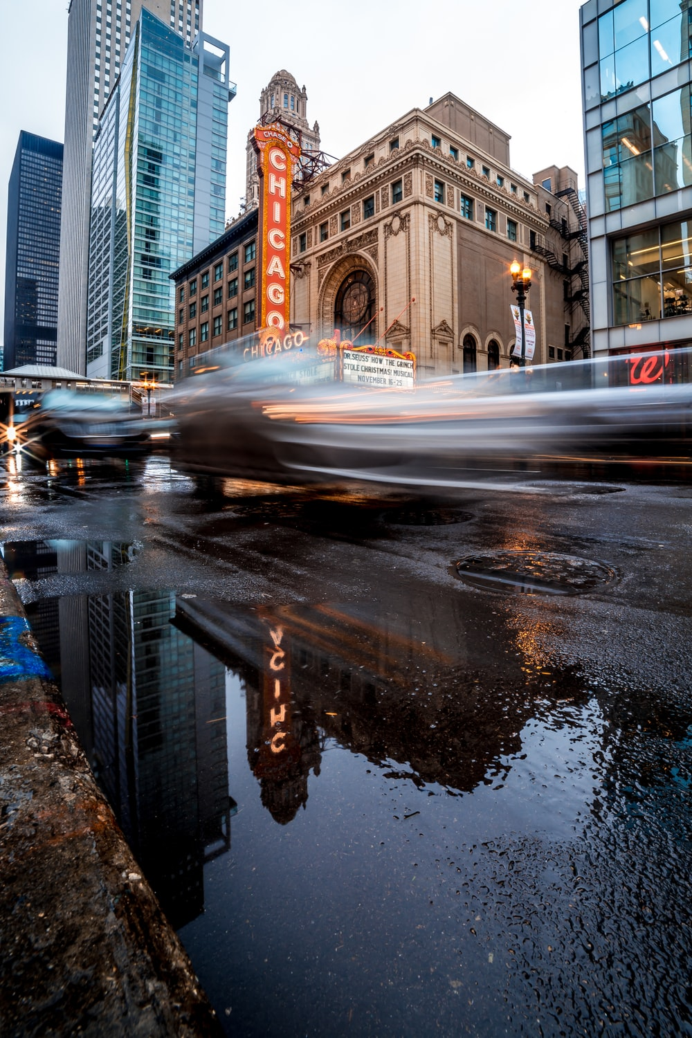 timelapse photography of vehicles on roadway near buildings