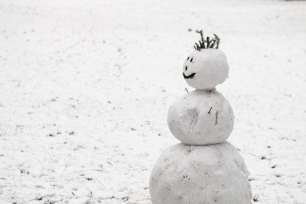 snow made snowman on snow covered field during daytime