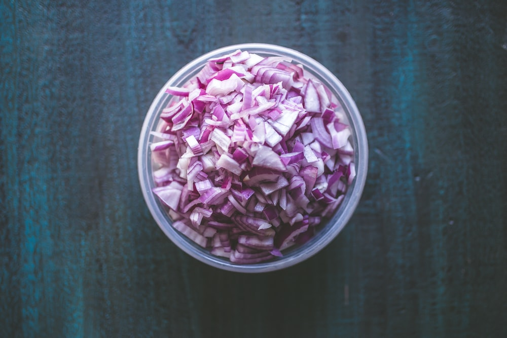 sliced onions on white container