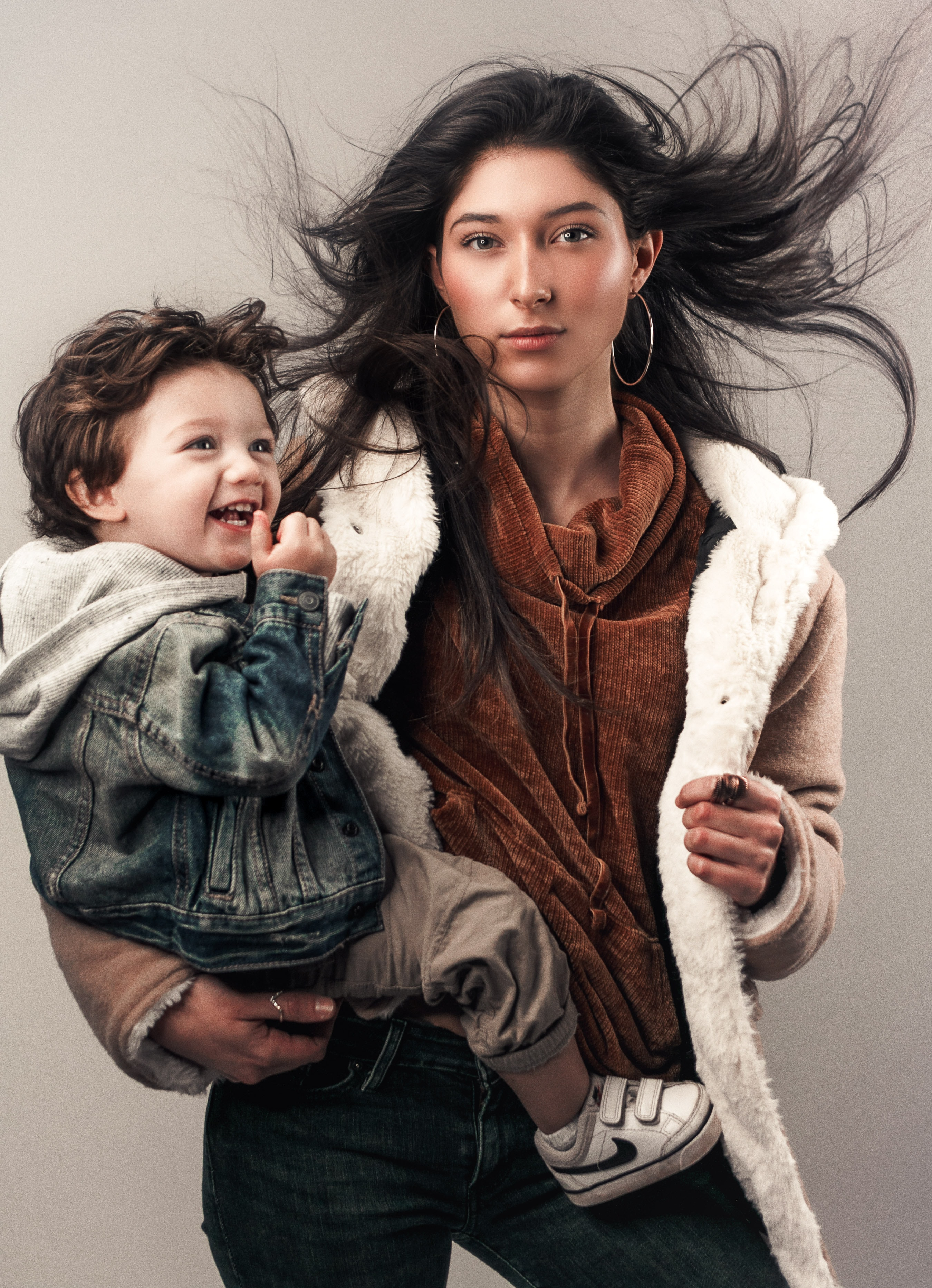 woman wearing white and brown coat while carrying a baby