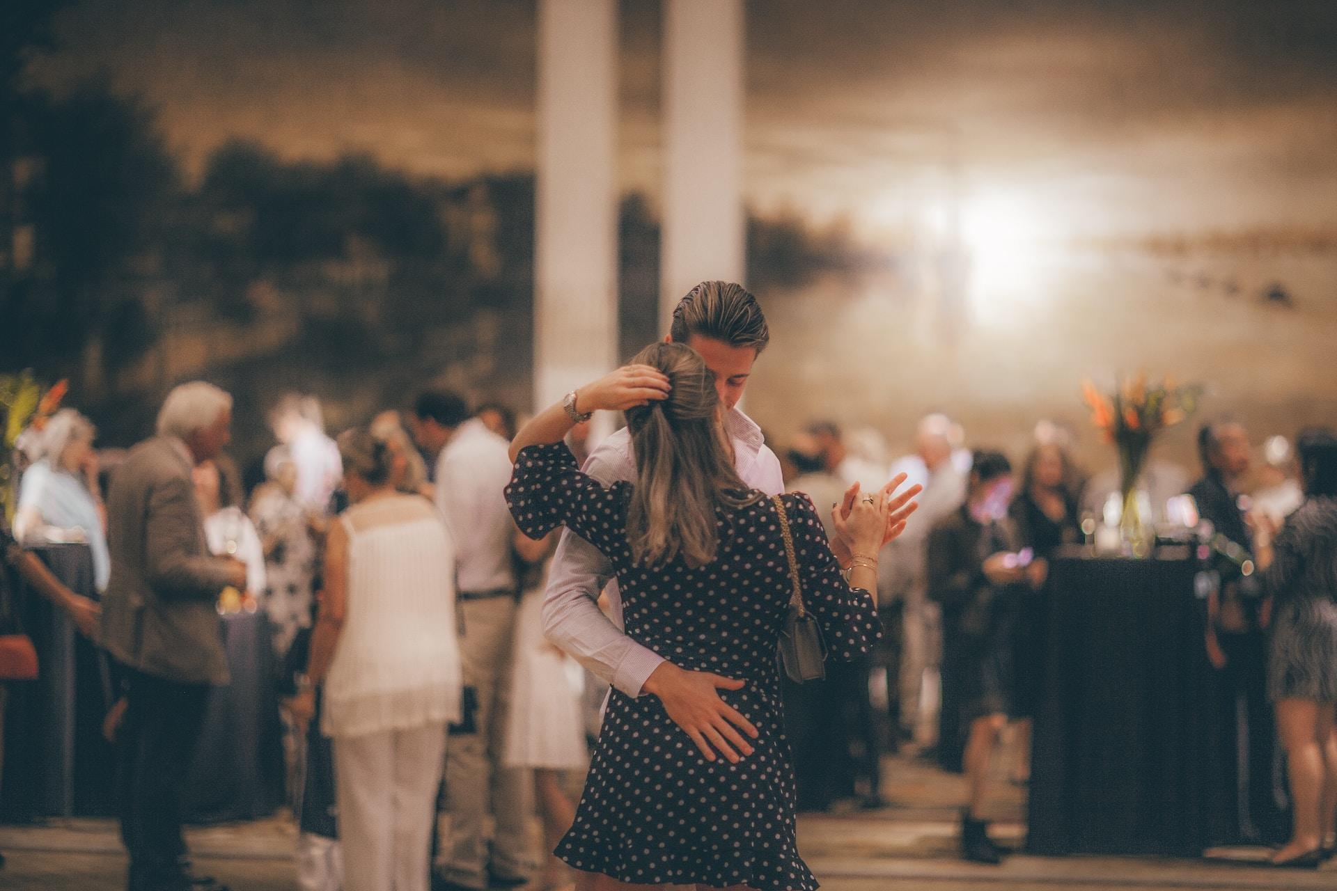 woman in polka-dot dress dancing with man in white dress shirt