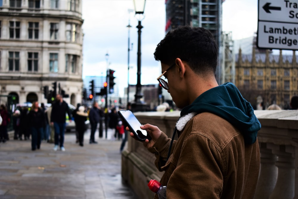 man standing and using phone near people