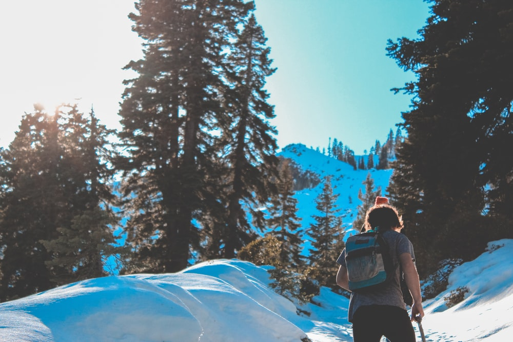 man waking on snow ground while carrying backpack