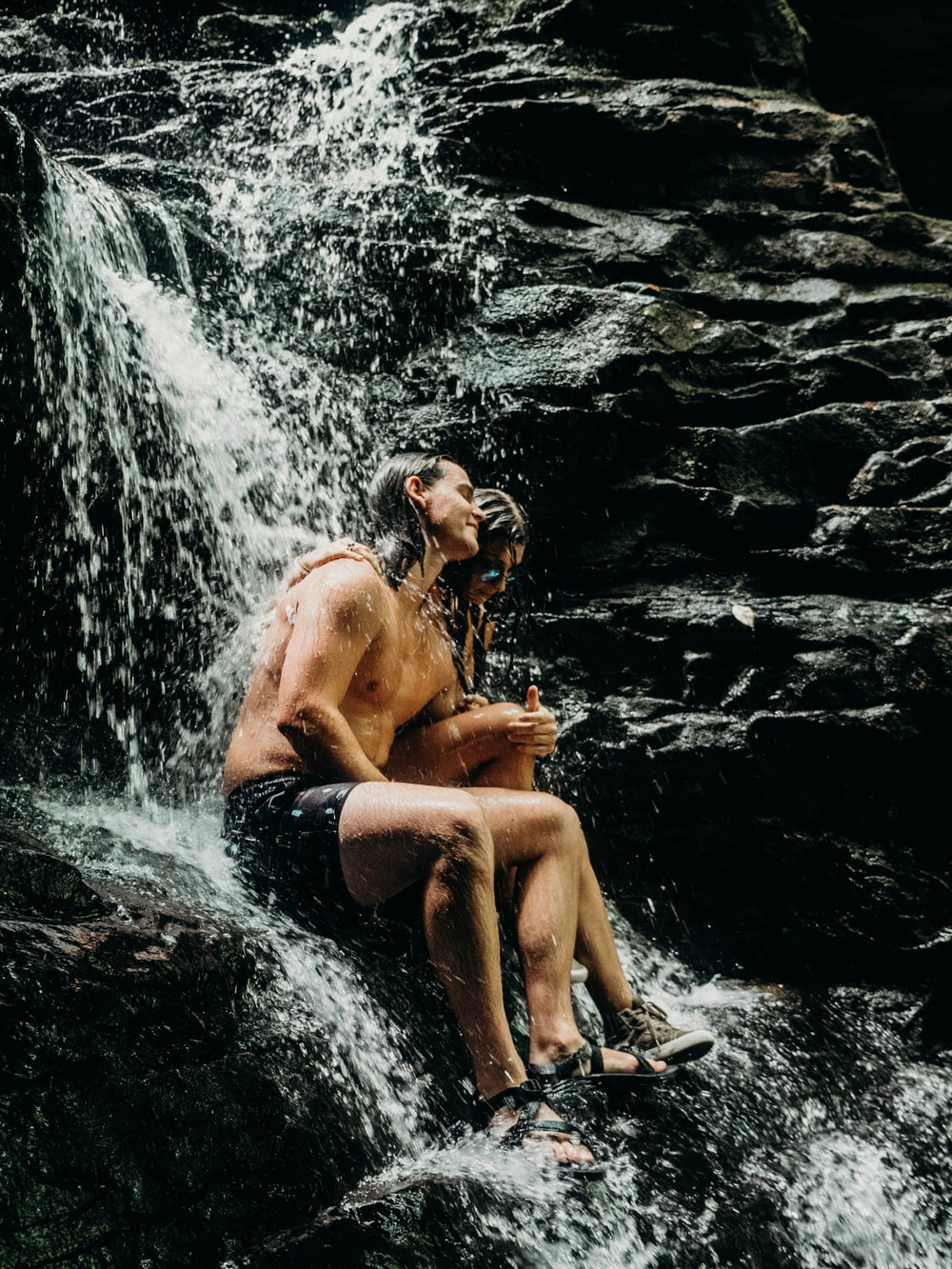 woman and man sitting on the waterfalls rock
