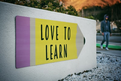 love to learn pencil signage on wall near walking man education zoom background