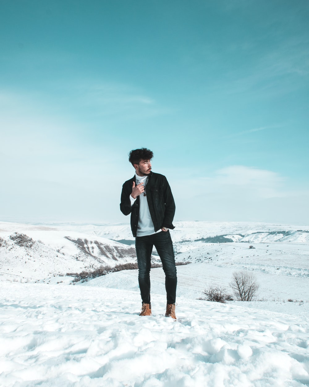 man standing on snow-covered field during daytime