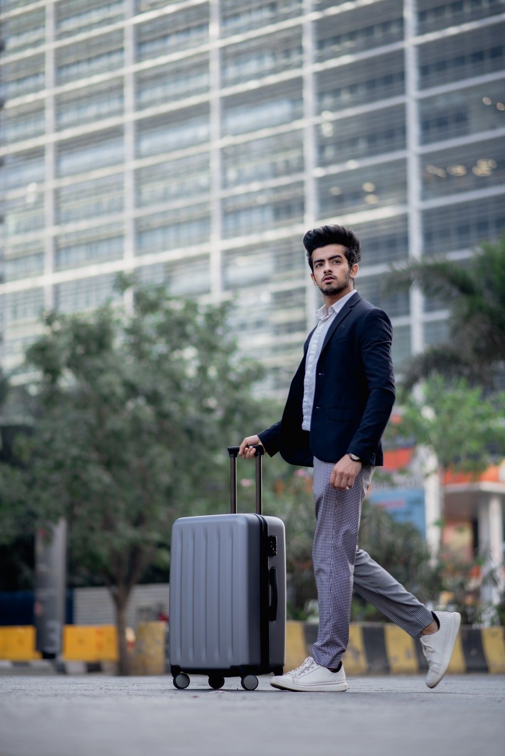 selective focus photography of man pulling luggage along concrete road