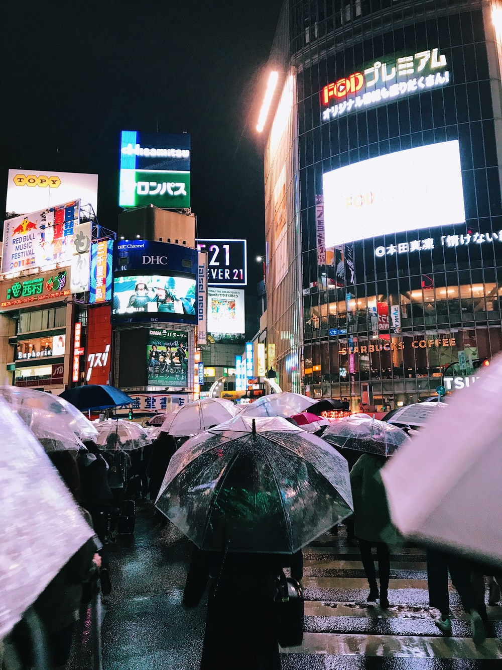 people with umbrellas walking near buildings during night